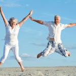 白人の老夫婦が浜辺で嬉しそうに手を上げてジャンプしている写真