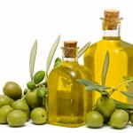 オリーブの実とガラス瓶に入った黄色いオリーブオイルの写真