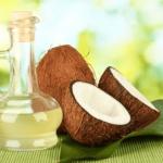 瓶に入った半透明なココナッツオイルとココナッツの実の写真