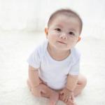 座ってこちらを見ている白い服を着た赤ちゃん